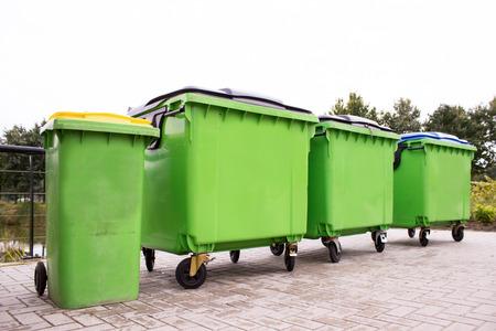 camion de basura: Contenedores de basura Greeen en una fila a lo largo de la calle