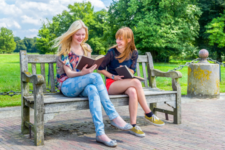 dutch girl: Caucasian teenage girls sitting on wooden bench in green park reading books