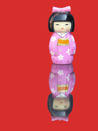 mirror image: Porcelain chinese figurine with mirror image isolated on red background