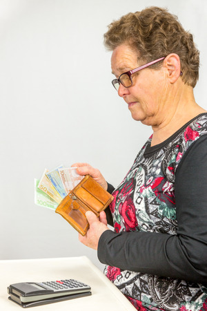 household money: Elderly caucasian woman counting euro money in wallet isolated on grey background