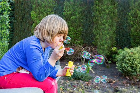 soapy water: Young dutch girl blowing bubbles from soapy water in garden outdoors Stock Photo