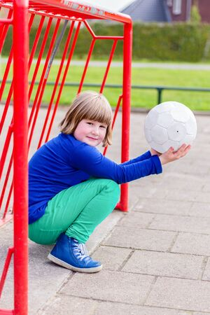 dutch girl: Young crouching dutch girl with white ball on hands in red metall goal on playground
