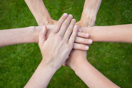 uniting: Several arms uniting above grass as symbol of friendship Stock Photo