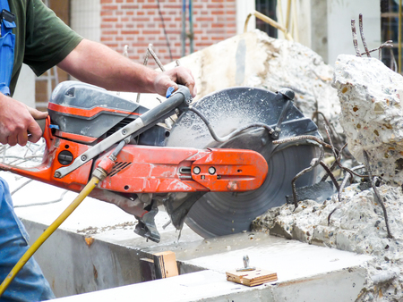 the concrete: Arms of construction worker holding grinder cutting Stock Photo