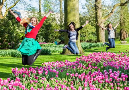 simultaneous: Three caucasian girls jumping above flowers field in Keukenhof Holland Editorial