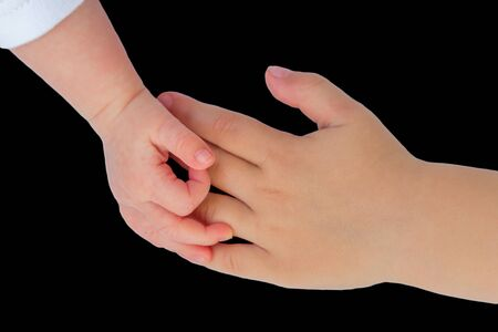upgrowth: Hand of newborn baby touching hand of child isolated on black background