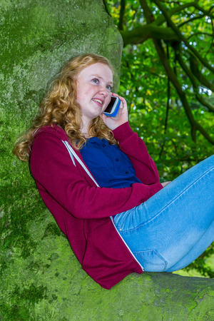 dutch girl: Dutch Caucasian teenage girl calling with mobile phone in green tree