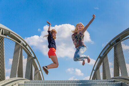 spontaneous expression: Two happy and enthusiastic teenage girls jumping on bridge in front of blue sky