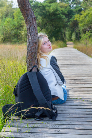 dutch girl: Blonde dutch teenage girl sitting on wooden path in nature with backpack Stock Photo