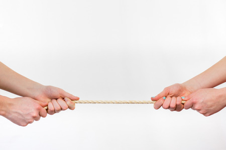 Two opposite persons pulling rope. Four arms isolated on white background