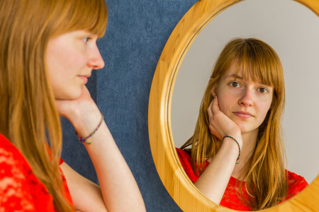 mirror face: Caucasian redhead teenage girl looking in mirror