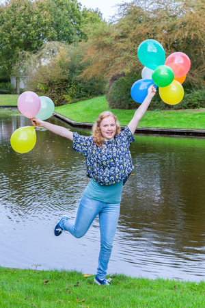 spontaneous expression: European teenage girl holding up many  coloured balloons at water of pond