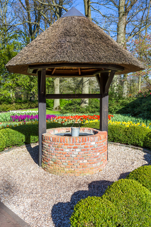 pent: New brick waterwell with bucket in park in netherlands Stock Photo