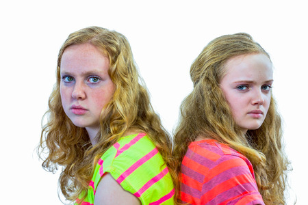 backs: Two angry european teenage sisters with backs touching isolated on white background