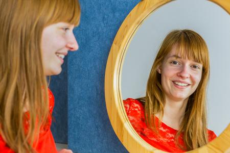 mirror image: Portrait of caucasian redhead teenage girl looking in mirror
