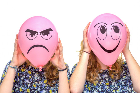 bitchy: Two girls holding pink balloons with facial expressions of frustrated and smiling face isolated on white background