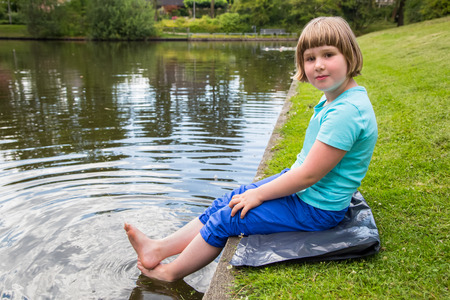 dutch girl: Young dutch girl sitting with feet in water of  pond in park