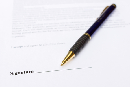 entrepeneur: Pen for signature lying on white contract paper