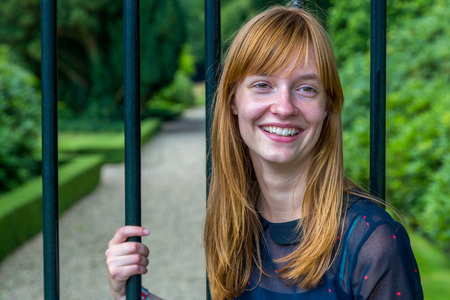 dutch girl: Red haired dutch teenage girl laughing holding metal bar of gate