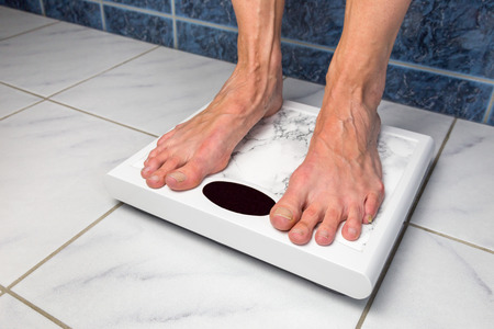 underweight: Female feet standing on bathroom scales for measuring body weight