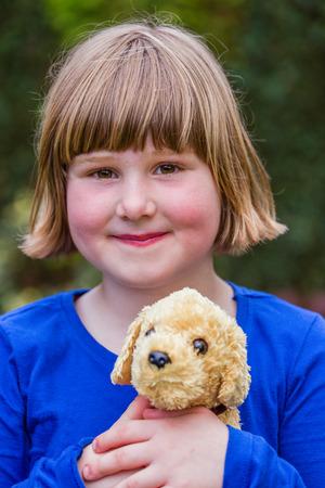 dutch girl: Young dutch girl holding hugging stuffed dog