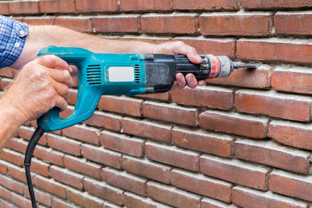 Arms of construction worker holding drilling machine against brick wall