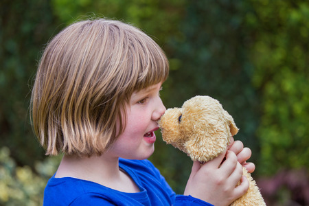 touching noses: young caucasian girl hugging stuffed dog against her nose