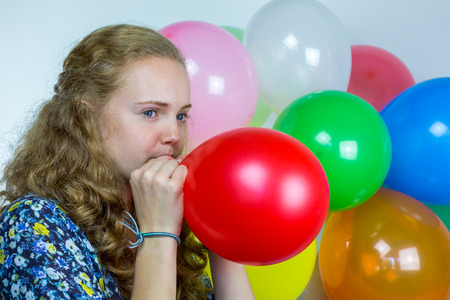 dutch girl: Dutch teenage girl blowing inflating colored balloons for birthday party