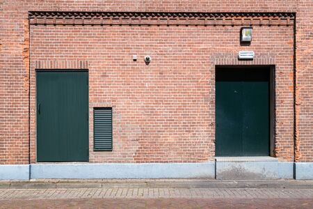 backdoor: Old brick wall with green doors and street