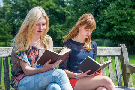 Two caucasian teenage girls reading books on bench in green nature