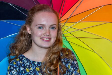 dutch girl: Blonde dutch teenage girl under umbrella with various colours Stock Photo