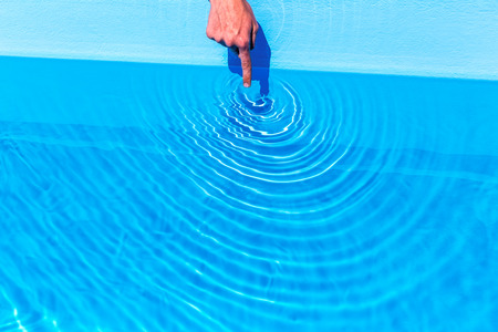 Forefinger making waves as circles in blue swimming pool