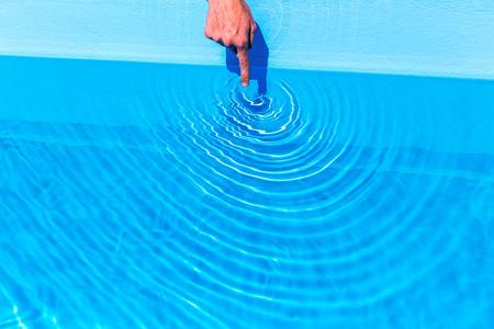 circulos concentricos: El índice haciendo olas como círculos en piscina azul Foto de archivo