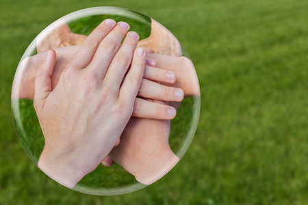 uniting: Hands uniting joining in glass ball isolated on green grass