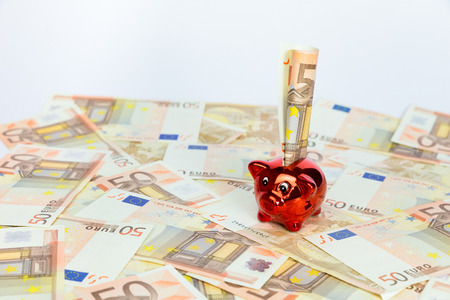 red bills: Small red piggy bank standing on many spread euro bills