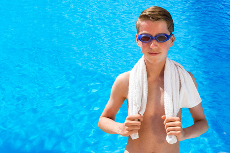 watersports: European teenage boy wearing swimming goggles and white towel at blue swimming pool