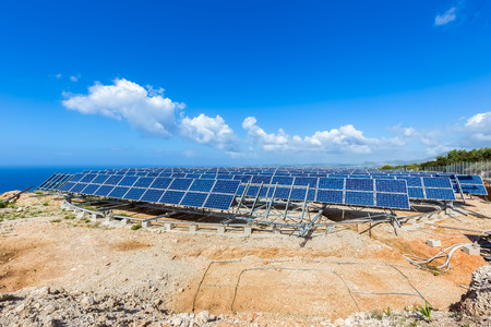 moveable: Field of many solar panels in rows on rotatable metal construction near blue sea in greece