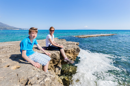 kefallinia: Mother and son as tourists sitting on rock at sea Stock Photo