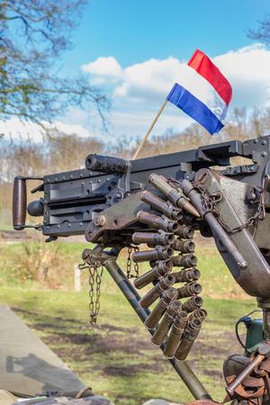 dutch flag: Military machine gun with bullets and dutch flag Stock Photo