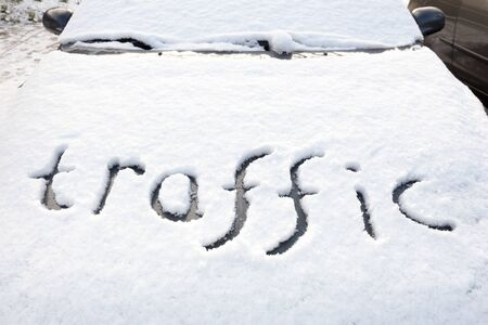 fallout: Word traffic written in snow on hood of car during winter season