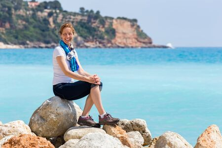 kefallinia: Caucasian middle aged woman as tourist sitting on rocks near blue sea enjoying vacation Stock Photo