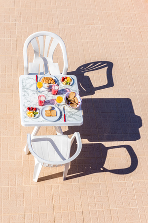 two chairs: Food for breakfast on table with two chairs at terrace