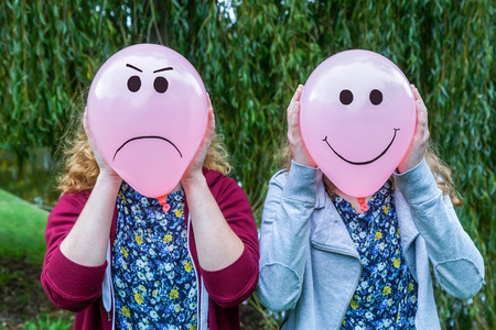 Two teenage girls holding balloons with smiling and angry facial expressions outdoors Stockfoto