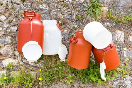 milk cans: Plastic white and brown milk cans hanging at wall in Greece Stock Photo