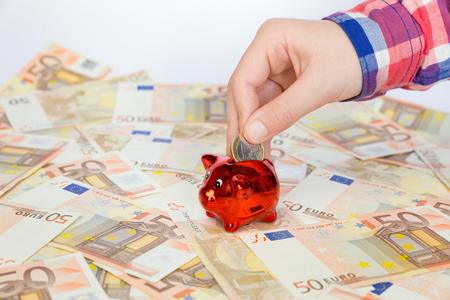 billets euros: Main de l'enfant en mettant euro pi�ce de monnaie dans la tirelire rouge sur de nombreuses notes propagation de la zone euro