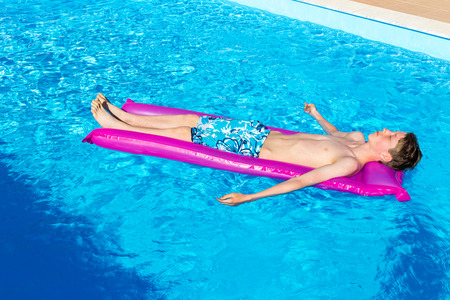 ly: Caucasian teenage boy lying  on air mattress in swimming pool as tourist on vacation in summer