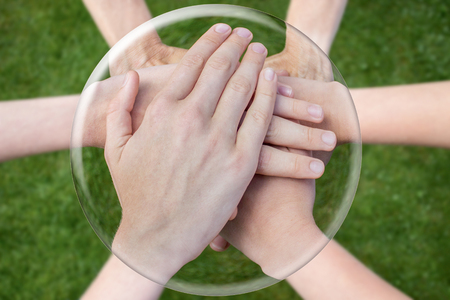 uniting: Hands arms above grass uniting joining in glass sphere