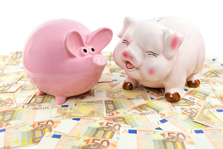 emptied: Two pink piggy banks on spread euro notes isolated on white background Stock Photo