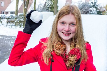 dutch girl: Young caucasian woman dressed in red holding snowball to throw in winter Stock Photo
