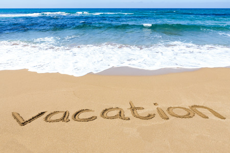 kefallinia: Word vacation written in sandy beach at coast with blue sea and waves